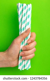 Woman is holding green and white paper straws in hand on bright background. Event and party supplies. Earth pollution concept. Copy space
