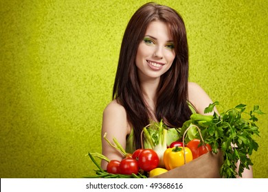 woman holding a grocery bag full of fresh and healthy food isolated on green background