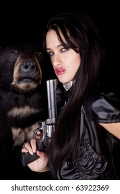 A woman is holding a gun by a black bear.