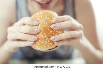 Woman holding hamburger and sitting at the table