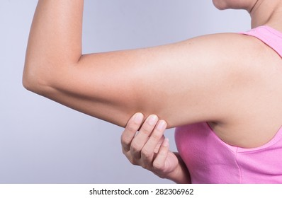 woman holding a hand with excess fat.