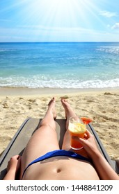 Woman holding in hand glass with drink and lying on a sun lounger on sandy beach. Summer vacation by the sea.