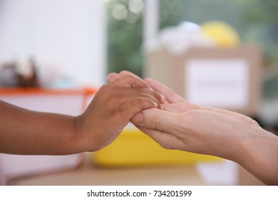 Woman holding hand of little African-American child on blurred background. Volunteering abroad concept