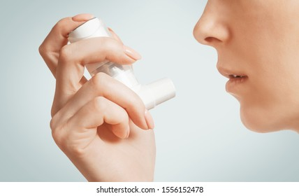 Woman holding in a hand medical asthma inhaler near her face, close-up.
