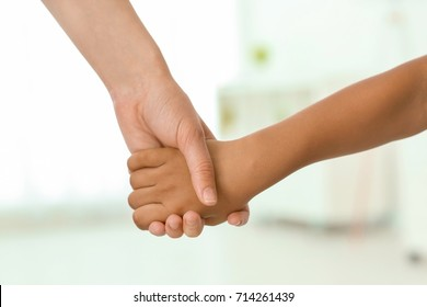 Woman holding hand of small African-American child on light background. Adoption concept