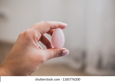 Woman holding in hand a vaginal (yoni) egg. Rose quartz crystal egg. Copyspace