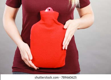 Woman holding in hand warm hot water bottle in red soft fleece cover, on grey. Health care, pain relievers, treatment objects concept.