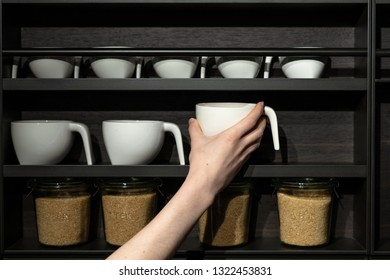 Woman holding in hand white tea or coffee ceramics cup against black kitchen wood shelf with design component