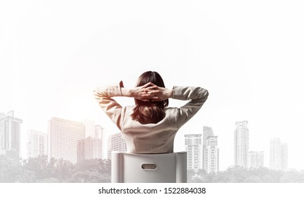 Woman holding hands behind head. Back view relaxed long haired woman in white suit sitting on white chair. Have a break concept with modern cityscape. Template for advertising and promotion.