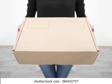 Woman holding in hands carton box closeup.