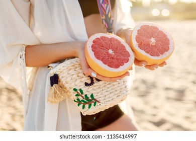 Woman holding in hands grapefruit halves . Pretty girl posing on summer beach with citrus fruits. Wearing boho outfit and straw bag.