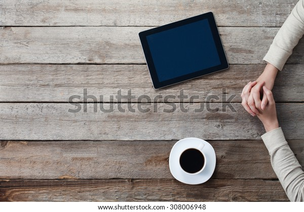 woman holding hands on a table with a tablet next to her