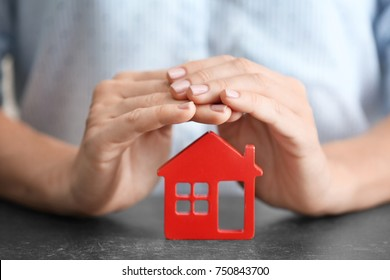 Woman holding hands over wooden figure of house at table, close up