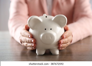 Woman holding in hands piggy bank at the table