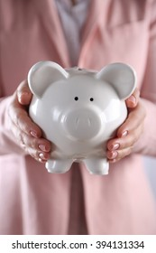 Woman holding in hands piggy bank, close up