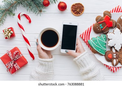 A woman holding in hands smart phone, coffee cane against decorations, gift boxes and plate with gingerbreads on a white wooden background.
