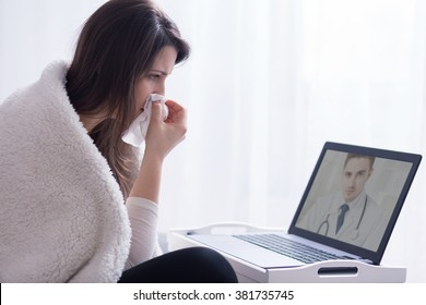 Woman holding hanky during consultation with skype doctor