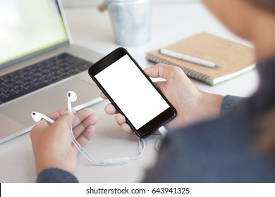 woman holding headphone and phone white screen on table third person view