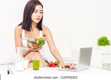 Woman holding healthy fresh salad in a bowl and working on a laptop computer while relaxing on sofa at home.dieting concept.healthy lifestyle with green food