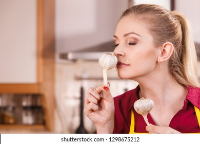 Woman holding healthy herb, two fresh natural garlic smelling it. Healthy eating and dieting concept.