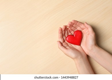Woman holding heart on wooden background, top view with space for text. Donation concept