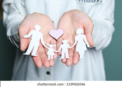 Woman holding heart and paper family cutout, closeup