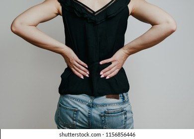 The woman is holding her back. Back pain, loins. The woman suffers from pain after increased effort. Rest concept. Spine pain in women.