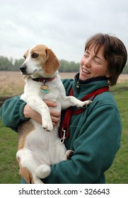 Woman holding her beagle