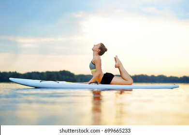 Woman holding her feet laying on sup board