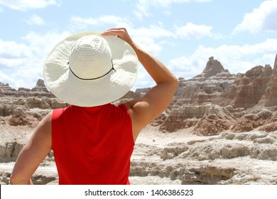 A woman holding her hat in the Badlands National Park in South Dakota.