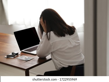 Woman holding her head in debt