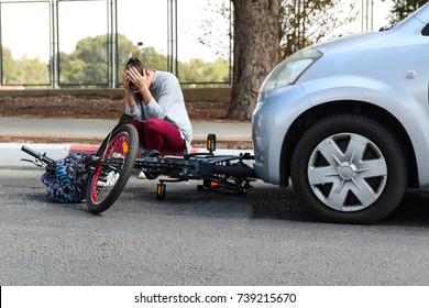 A woman holding her head near a traffic accident between electric e bike and car
