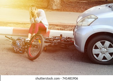A woman holding her head near a traffic accident between electric bike and car