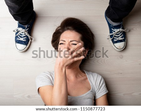Woman holding her nose against the smell of feet in sneakers standing on either side of her head viewed looking down