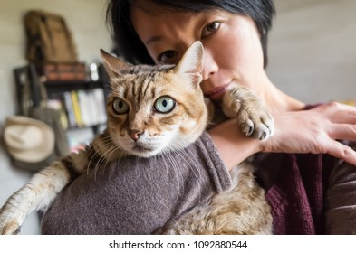 woman holding her old cat in the house