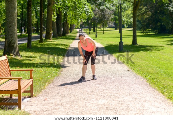 Woman holding her painful knee after exercising in park