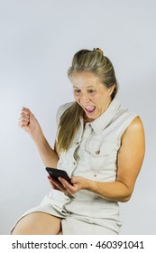 Woman holding her phone with a cheerful and excited look.