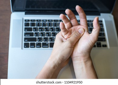 Woman holding her wrist pain from using computer.,Hand pain