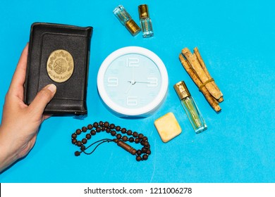 woman holding holly muslim book and rosary, siwak, perfume on pink background