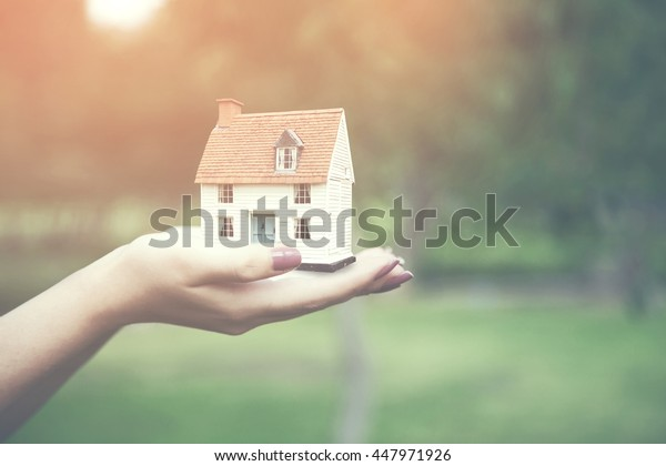 woman holding home model, loan concept