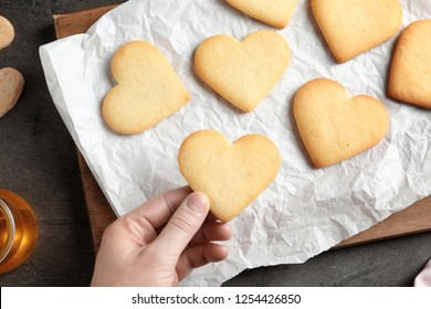 Woman holding homemade heart shaped cookie over table with pastry, top view