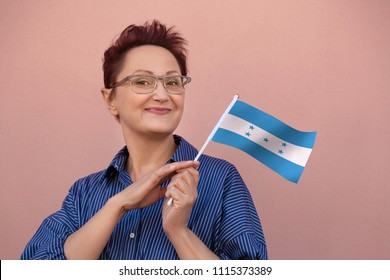 Woman holding Honduras flag. Nice portrait of middle aged lady 40 50 years old with a national flag of Honduras over wall background.