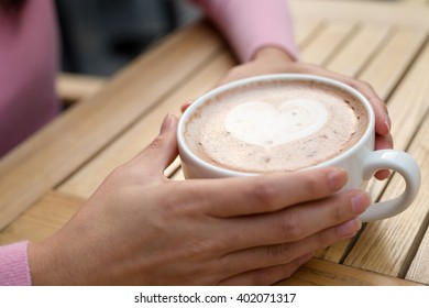 Woman holding hot coffee at outdoor cafe