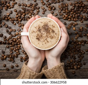 woman holding hot cup of coffee, view from the top
