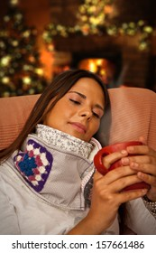 Woman holding Hot Drink during Christmas night seating at her home waiting for presents