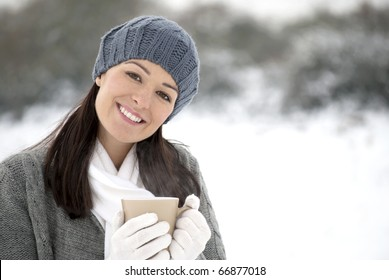 Woman holding hot drink outside in the snow