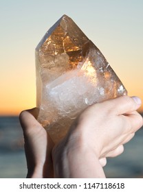 Woman holding huge natural Citrine Cathedral Quartz from Brazil in her hand at sunrise in front of the lake.