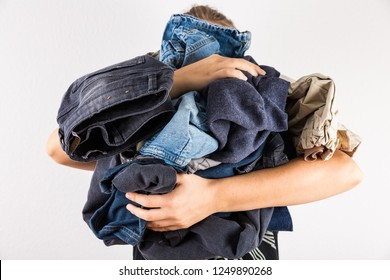 Woman holding huge pile of clothes - laundry concept