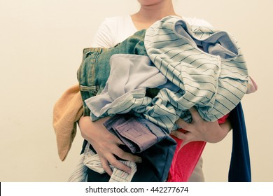 Woman holding a huge pile of clothes . concept Laundry and Clothing