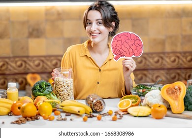 Woman holding human brain model with variety of healthy fresh food on the table. Concept of balanced nutrition for brain health